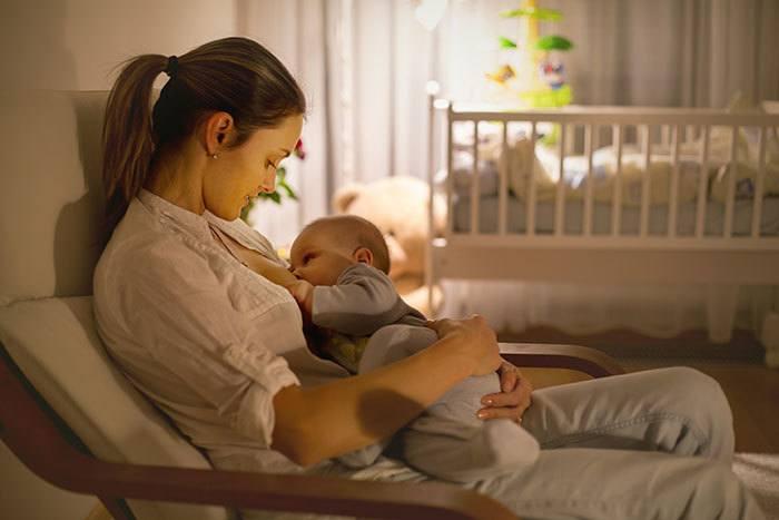mother breastfeeding baby in bedroom